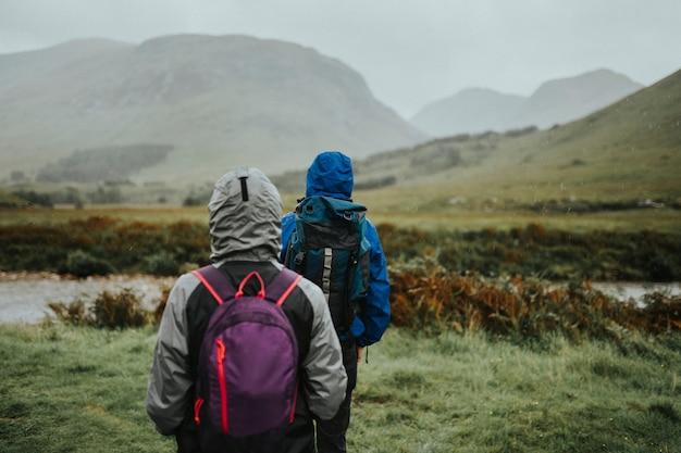 高地の雨の中トレッキングカップル