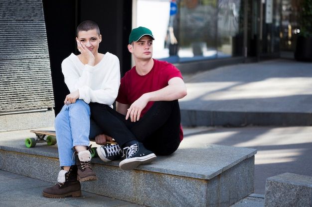 Couple in trendy clothes sitting on border near longboard
