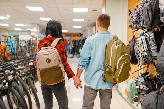 Пара примеряет рюкзаки для путешествий, покупок в спортивном магазине. летний сезон экстремальный образ жизни, магазин активного отдыха, покупатели туристического снаряжения