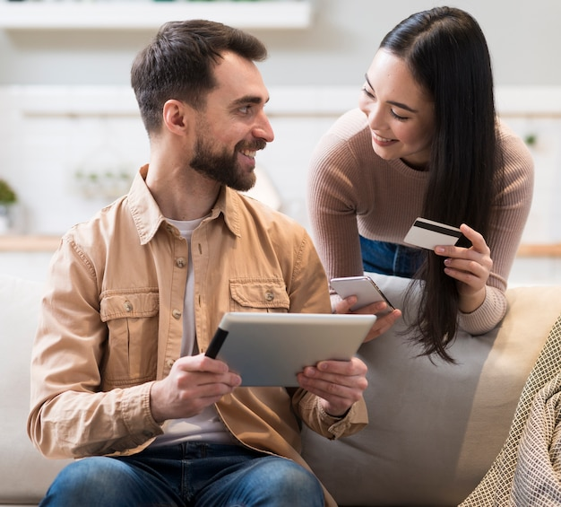 タブレットとクレジットカードでオンラインショッピングをしようとしているカップル
