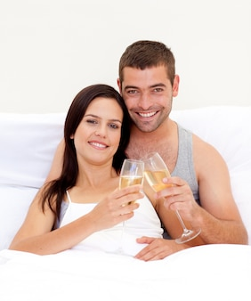 Couple tusting with champagne in bed