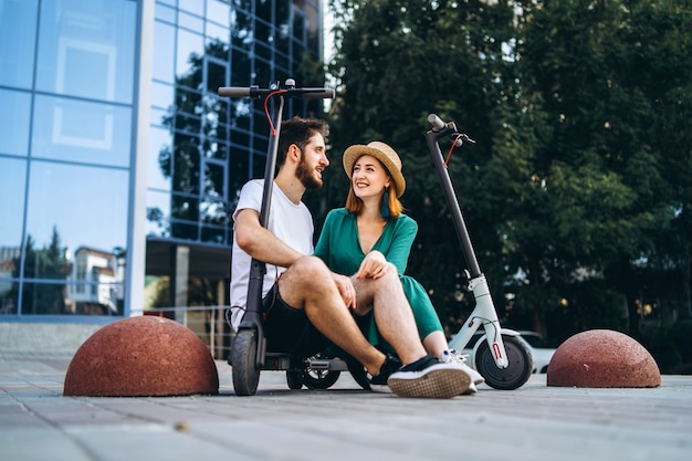 Couple of two attractive people are chilling near the glass building with their electro scooters. man and woman enjoy vacation