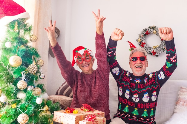 Couple of two crazy and funny seniors playing having fun together and celebrating doing a party at home the christmas day before wrap the presents and gifts