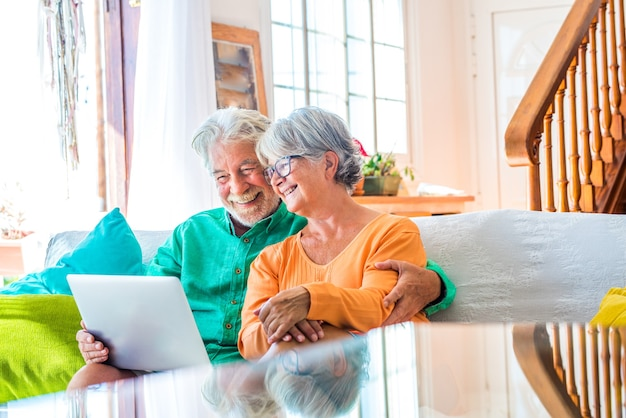 Couple of two happy mature and old people or seniors at home sitting on the sofa enjoying and having fun together looking and using a laptop or computer pc