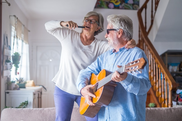 Couple of two happy seniors or mature and old people singing and dancing together at home indoor. retired man playing the guitar while his wife is singing with a remote control of tv.