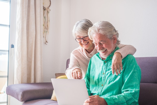 Couple of two old and mature people at home using tablet together in sofa. senior use laptop having fun and enjoying looking at it. leisure and free time concept