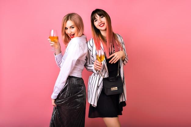 Coppia di due donne eleganti piuttosto divertenti che bevono champagne e si godono il tempo della festa, abiti eleganti in bianco e nero glamour, capelli rosa alla moda