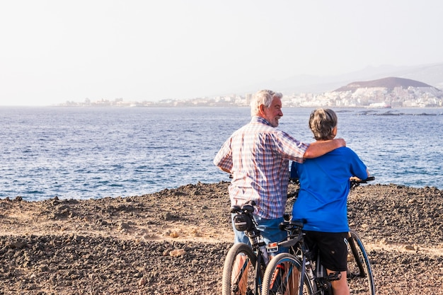 Couple of two senior and mature persons with their bikes in isolated zone looking at the water of the sea at the beach - fitness adults lifestyle