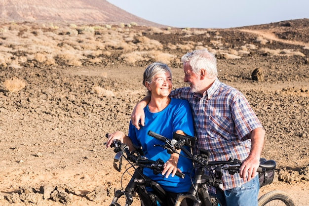 Couple of two seniors together in the mountains riding with their mountain bikes - happy, healthy and fitness lifestyle - woman and man mature having fun