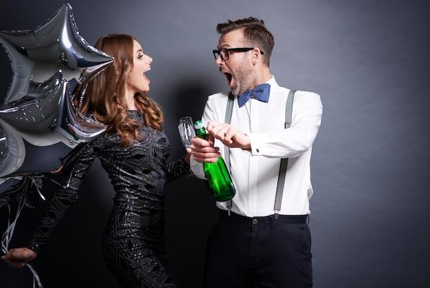 Пара откупоривает бутылку шампанского