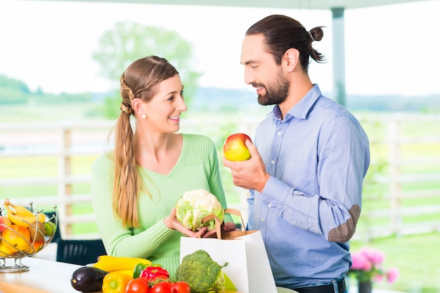 Couple unpacking grocery shopping bag at home