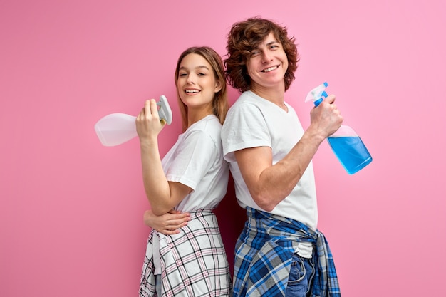 Couple use detergents for cleaning isolated on pink studio background.