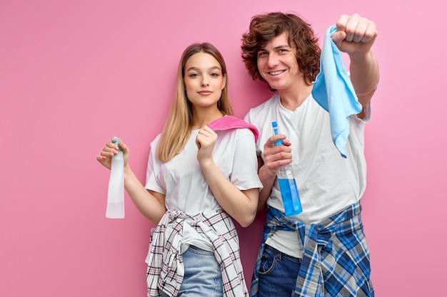 カップルは、ピンクのスタジオの背景に分離されたクリーニングに洗剤を使用しています。家族、人間関係、家事。