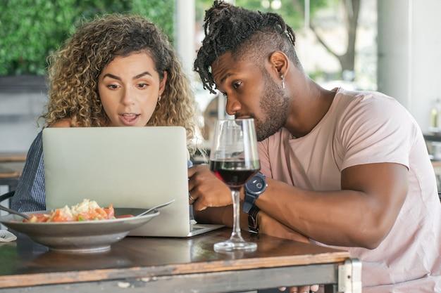 함께 점심을 먹으면서 노트북을 사용하는 커플.