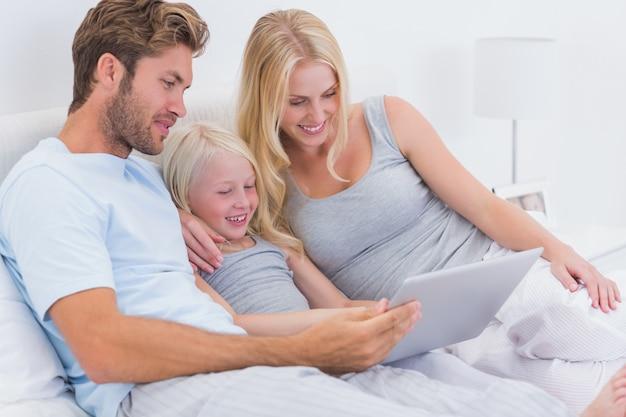 Пара, используя ноутбук с дочерью