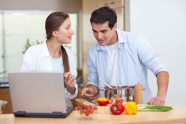 Пара, используя ноутбук, чтобы приготовить