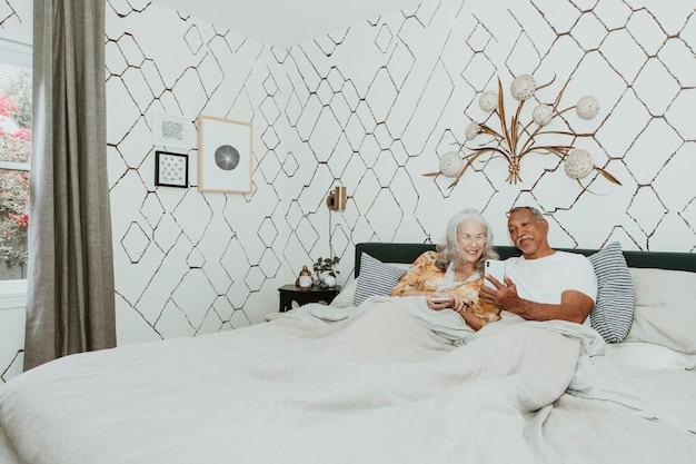 Пара с помощью телефона на кровати