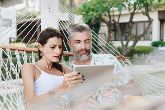 Пара с помощью планшета в гамаке