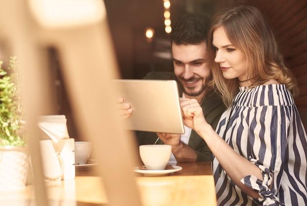 カフェレストランでデジタルタブレットを使用してカップル