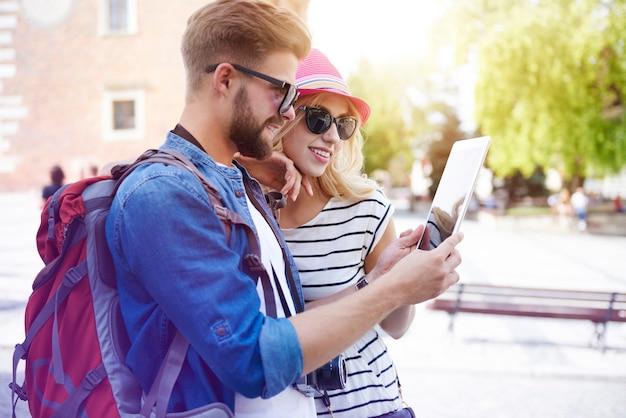 旅でデジタルタブレットを使用しているカップル