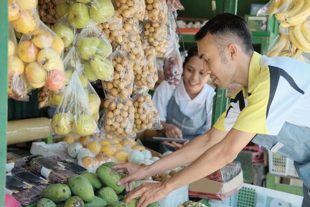 店を準備するときにマンゴーを選択しながらデジタルタブレットを使用してカップル
