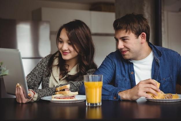 Пара с помощью цифрового планшета во время завтрака