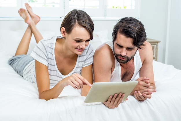Couple using digital tablet while lying on bed