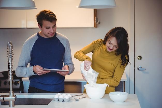 キッチンでクッキーを準備しながらデジタルタブレットを使用してカップル
