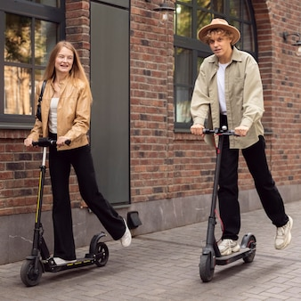 Couple using electric scooters outdoors