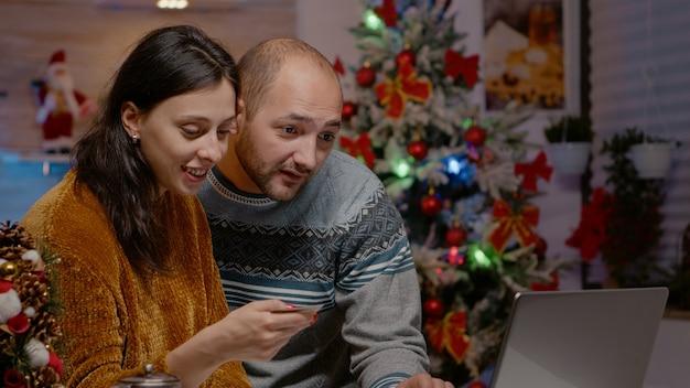 クリスマスの買い物にノートパソコンとクレジットカードを使用しているカップル
