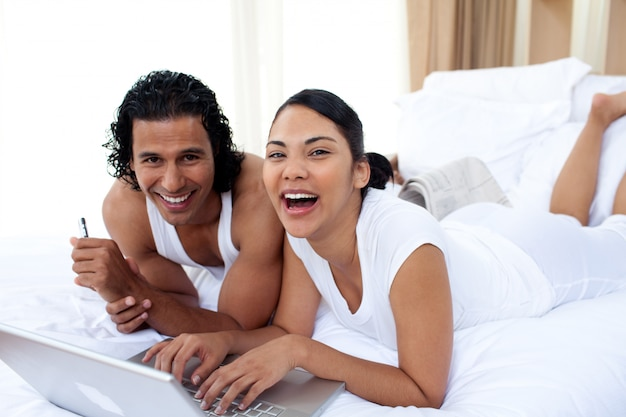 Couple using a laptop lying on the bed