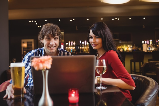 Couple using laptop while having drinks
