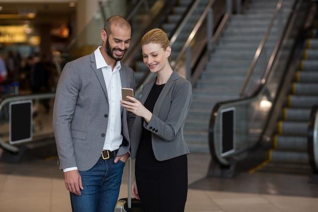 Пара, использующая мобильный телефон в аэропорту