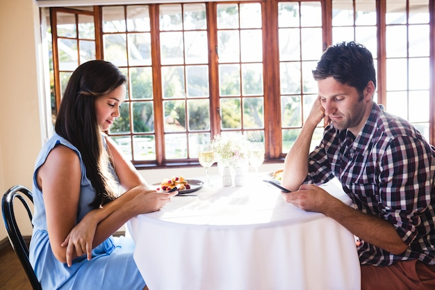 Couple using mobile phone in restaurant