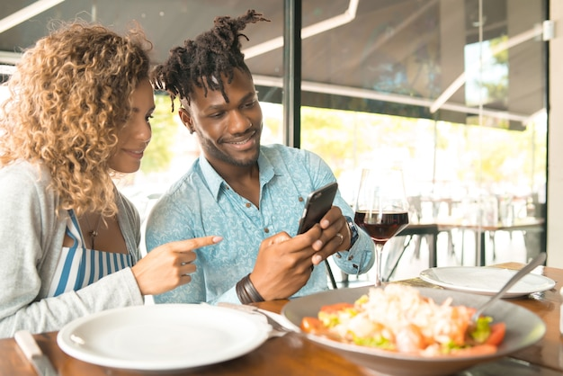 Couple using a mobile phone and spending good time together while having a date at a restaurant.