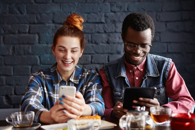 Пара, используя современные гаджеты во время отдыха в кафе. рыжая женщина читает информацию на веб-странице с помощью мобильного телефона, а черный человек смотрит видео на цифровой планшет