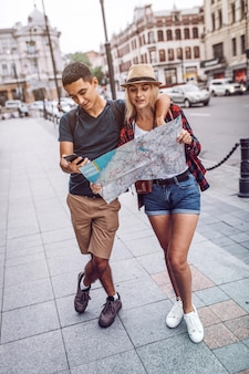 Couple using phone and map on street
