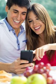 ロマンチックなピシニックでスマートフォンを使うカップル。