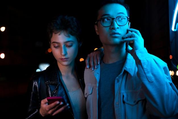 青いネオンの光の中で夜にスマートフォンを使用してカップル