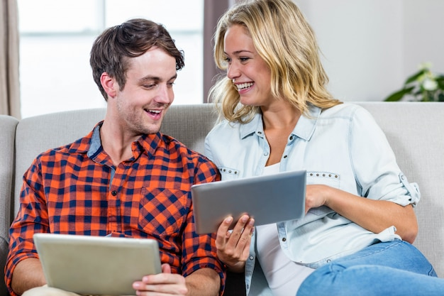 Couple using tablet computers on the couch