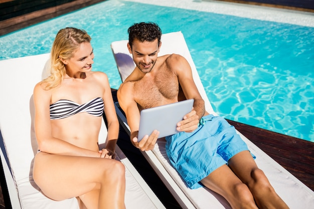 Couple using tablet on deckchairs by the pool