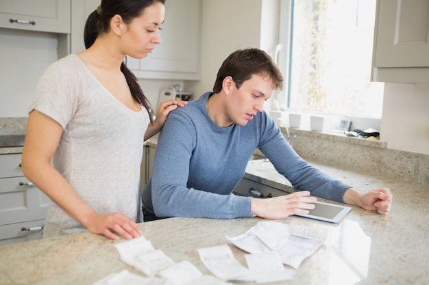 Couple using tablet pc to calculate finances