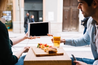Couple using tablet sitting in restaurant
