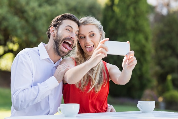 Couple using taking a selfie on mobile phone