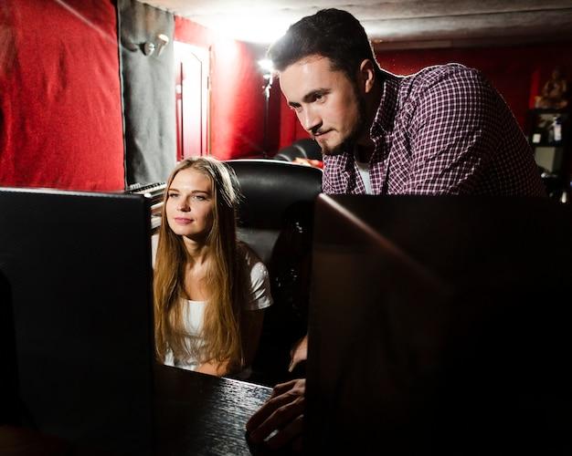 コンピューターを使用して音楽のミキシングとマスタリングを行うカップル