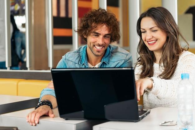 ランチを食べながらレストランでノートパソコンを使うカップル。