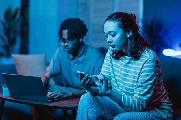 一緒に家にいる間に彼らの現代のデバイスを使用しているカップル