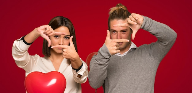 Couple in valentine day focusing face. framing symbol over red background
