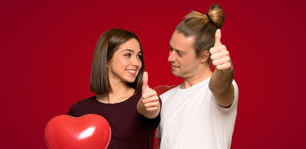 Couple in valentine day giving a thumbs up gesture over red background