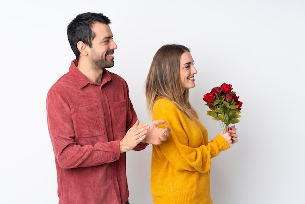 Couple in valentine day holding flowers over isolated wall applauding after presentation in a conference